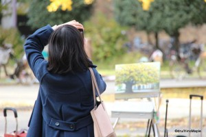 Woman Taking a Photo of the Famous Ginkgo with a Painting in Front of Her
